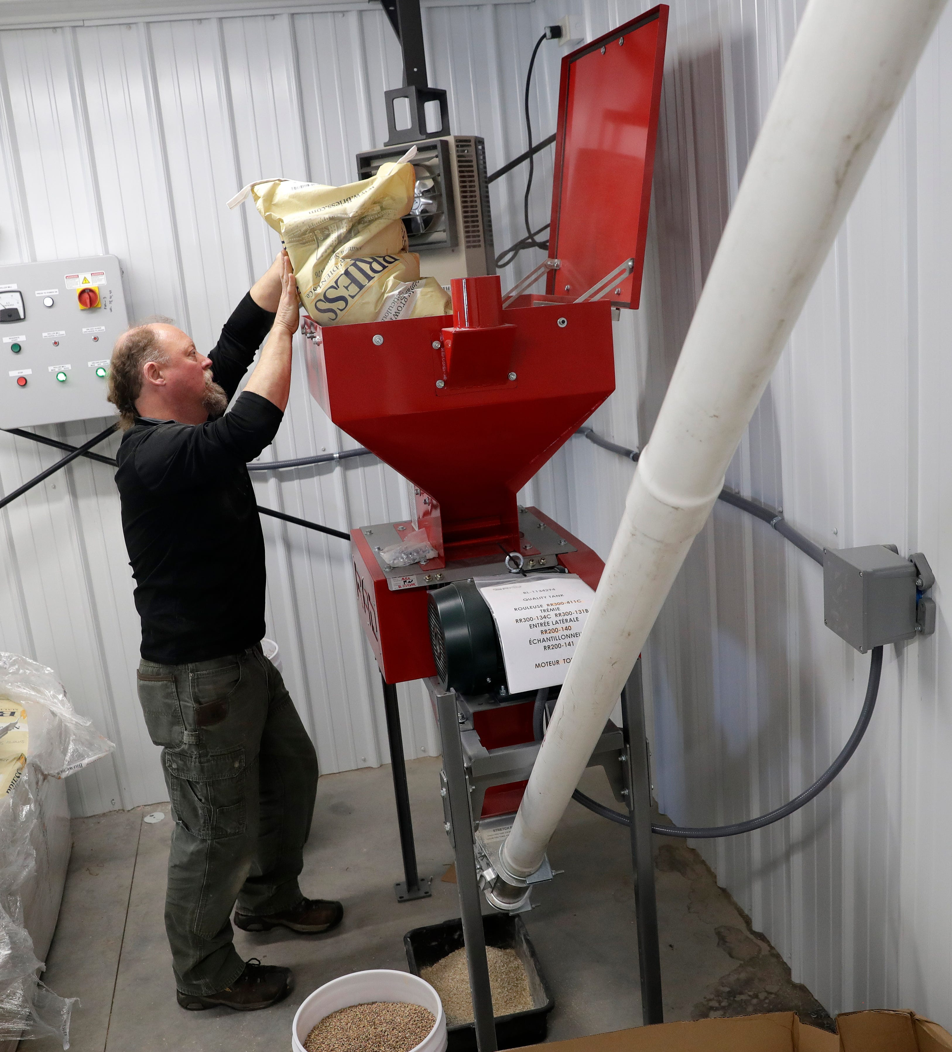 Badger Colish, a contractor with Quality Tank Solutions (the company that built the Zambaldi Beer brew system), feeds bags of malt into a gristmill during the first brew.