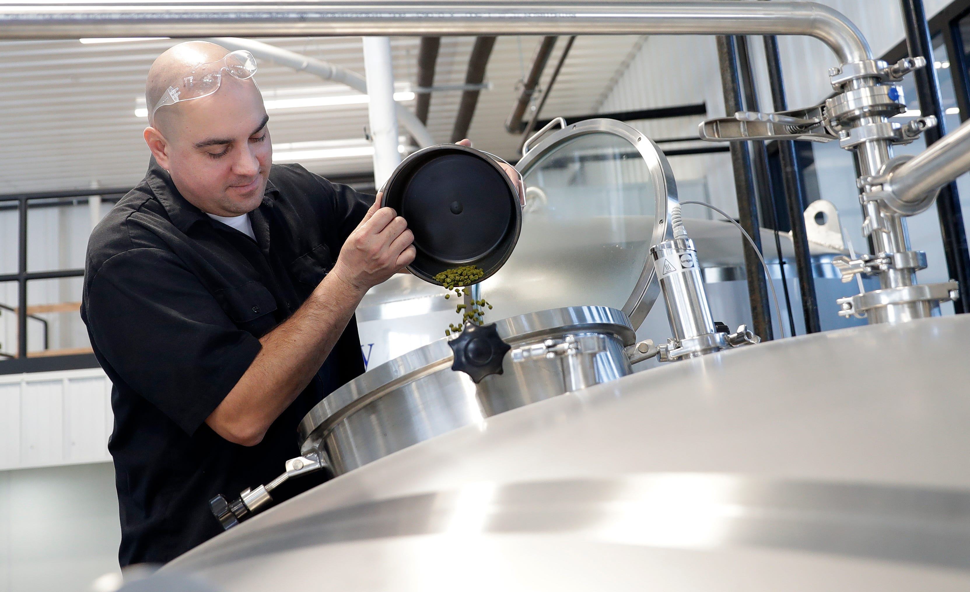 David Malcolm, co-owner of Zambaldi Beer, pours hops into a brewing tank while making his first batch of beer on Feb. 14 at the newly opened Allouez brewery and taproom.