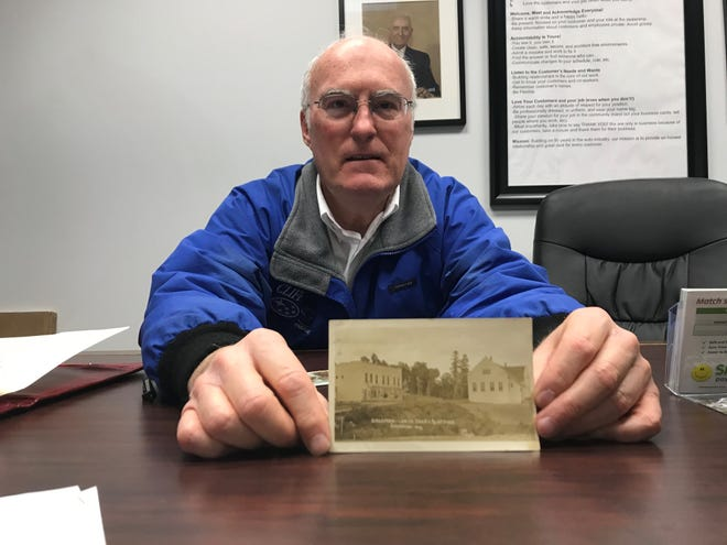 Clifford M. Wall displays a photo of a lumber company's store where his grandfather, C.C. Wall, worked in the 1920s. The lumber company store's sale of Model T cars to employees spurred C.C. Wall to pursue selling cars.