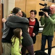 Bay Port High School chemistry teacher Anne Schmidt hugs her husband as her children join the celebration of her Golden Apple Award on Wednesday. Schmidt was among eight Brown County teachers surprised with the awards.