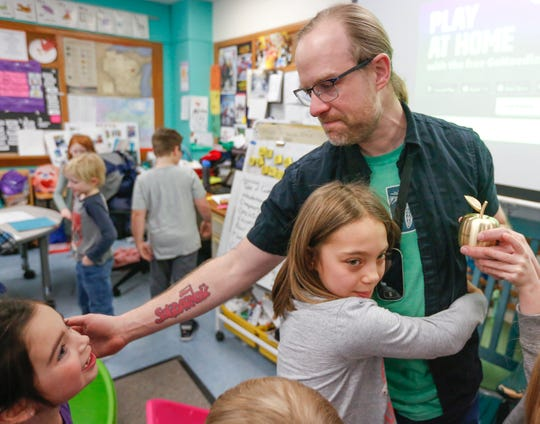 Ned Dorff's students hug and congratulate him after receiving the 2020 Golden Apple Award hosted by the Greater Green Bay Chamber and community members who surprised eight Greater Green Bay area teachers in their classrooms on Wednesday, Feb. 19, 2020, at Aldo Leopold Community School in Green Bay, Wis.
