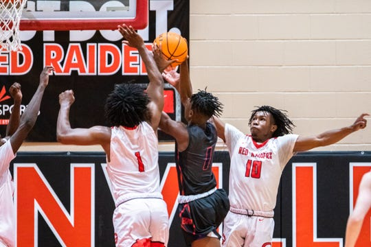 Belton's Sam Woods jumps up for a shot guarded by Greenville's Malik Norris and Greenville's Quentin Johnson during their game Tuesday, February 18, 2020.