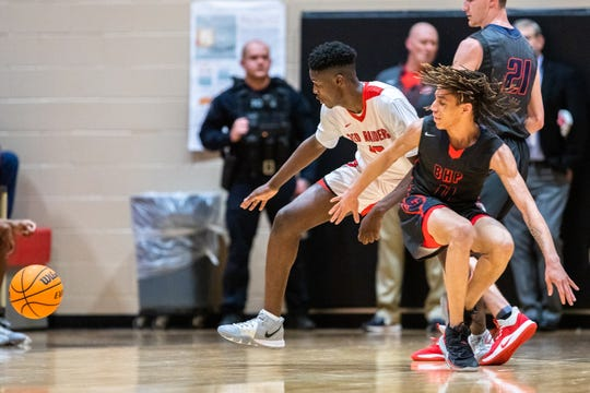 Greenville's Nijheer Holmes and Belton's Carletho Burgos look to recover possession of the ball during their game Tuesday, February 18, 2020.