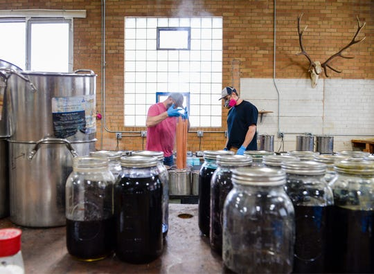 Shane Roady, left, and Xander English work on dyeing yarn in The Farmer's Daughter Fibers processing facility in Great Falls.