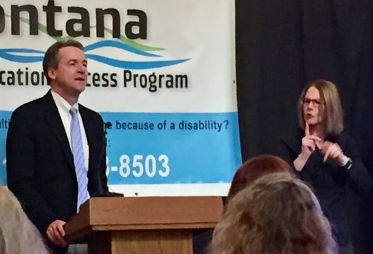 Gov. Steve Bullock speaks while a sign language interpreter assists during a speech Wednesday in Helena celebrating the Montana Telecommunication Access Program.