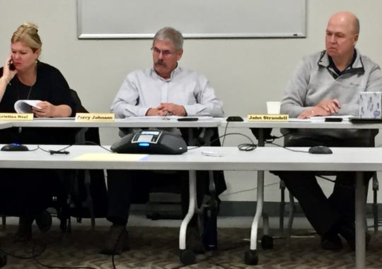 From left, POST staff Kristina Neal and Perry Johnson listen Wednesday in Helena to former Cascade County Sheriff Bob Edwards via telephone along with POST council member John Strandell.