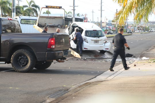 Guam Police Department officers load a white Toyota Yaris involved in a fatal accident onto a tow truck to haul from the Upper Tumon crash site on Feb. 20, 2020.