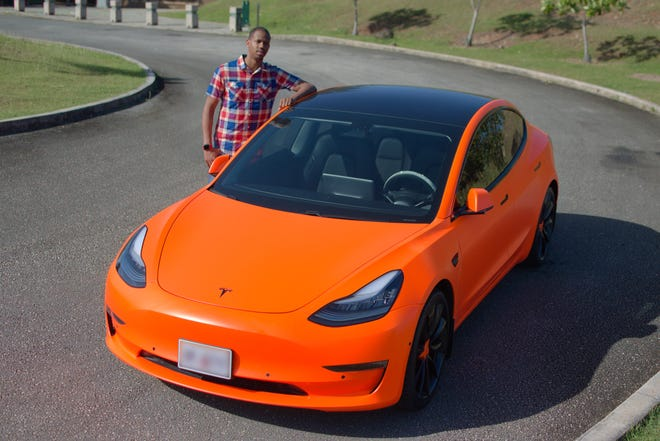 Delante Simpson stands with one of two of his Tesla Model 3s on Feb. 13, 2020, at the Asan Bay Overlook