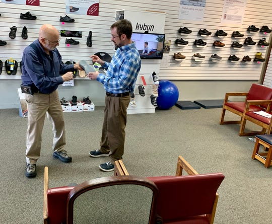 Terry Abeles and his son, Ted Abeles, examine the sole of a pair of shoes at T Abeles & Son in Ridgeland. The store specializes in the kybun and Joya brands.