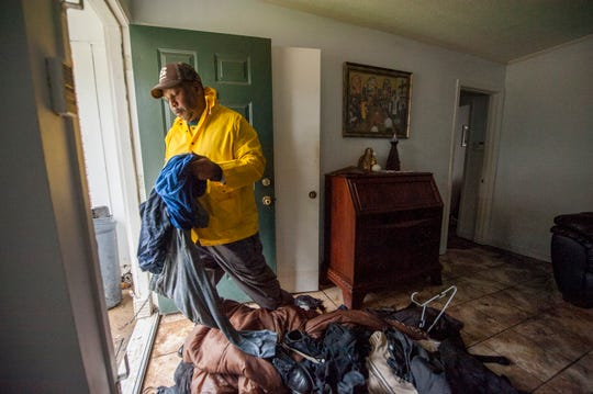 Van Miller works on sorting items soaked in his River Road house in Northeast Jackson Wednesday, Feb. 19, 2020, after Pearl River floodwaters started to recede.