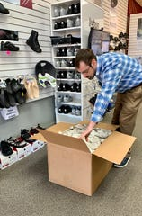 Ted Abeles opens a box at T Abeles & Sons in Ridgeland. The shoe store specializes in the kybun and Joya brands.