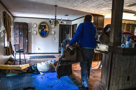 Jackson resident Jeff Sharp moves trash out of his brother Chris Sharp's home on River Road that was damaged by flood waters in Jackson, Miss. Wednesday, Feb. 19, 2020.