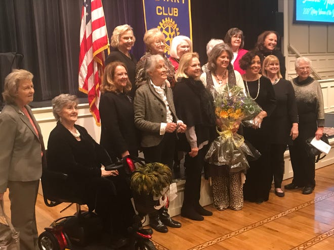 Suzanne Allison, holding flowers she received when she was announced as the Rotary Club's Woman of the Year, stops for a photo with 14 former honorees with the award.