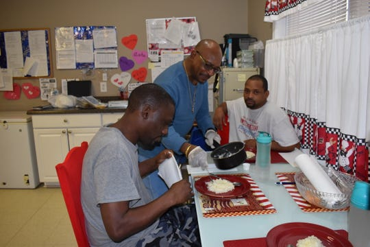 Walter Douglas serves breakfast to a couple of the clients he helps as a DSP for Madison-Haywood Developmental Services.