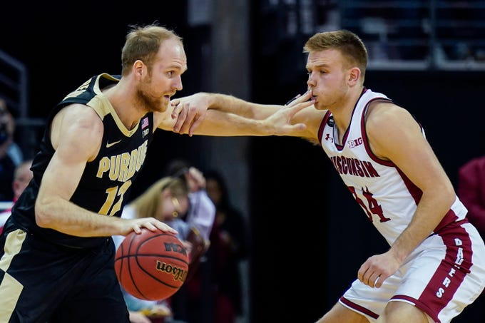 Purdue's Evan Boudreaux (12) drives against Wisconsin's Brad Davison (34) during the second half of an NCAA college basketball game Tuesday, Feb. 18, 2020, in Madison, Wis. Wisconsin won 69-65.(AP Photo/Andy Manis)