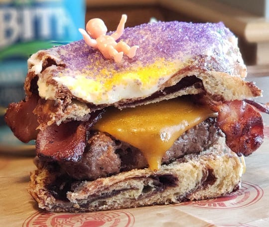 Mardi Gras Mambo Burger: an abomination or a savory, sweet combo made in heaven.Either way, this meal will make your jaw drop.  Burgersmith, a Baton Rouge burger joint, andCalandro's Supermarket's,a Baton Rouge grocery store, havea new creation. The cheeseburger, topped with bacon, is sandwiched betweenking cake — complete with icing, sprinkles and a king cake baby.