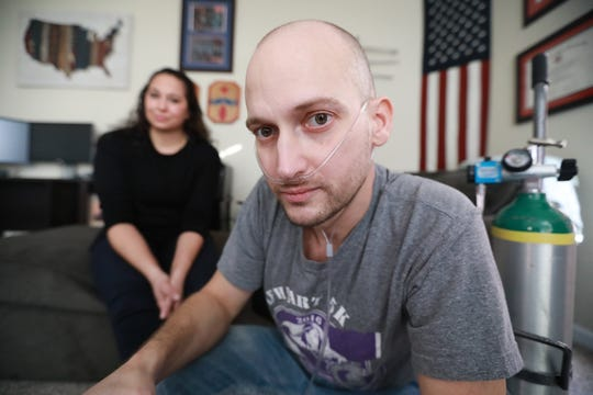 Heath Robinson of Pickerington suffered from exposure to toxic smoke from trash burning pits while serving in the Middle East and now suffers from a rare cancer that he likely soon will die from. His wife, Danielle, is behind him.
