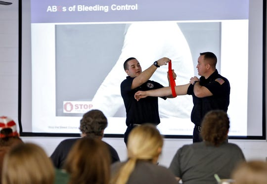 Lancaster Fire Department members John Leasure and Shawn Klaameyer (right) give instruction in how to tie a tourniquet at Lancaster High School  February 18, 2020.The staff of Lancaster High School and Generasl Sherman Jr. High were undergoing training on how to apply  tourniquets in a active shooter or emergency situation.[Eric Albrecht/Dispatch]