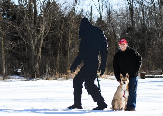 Chris Ketchum of Mason and, his dog Max, on Wednesday, Feb. 19, 2020 alongside the 8-foot-tall man-made Bigfoot in his backyard that Ketchum made from plywood.