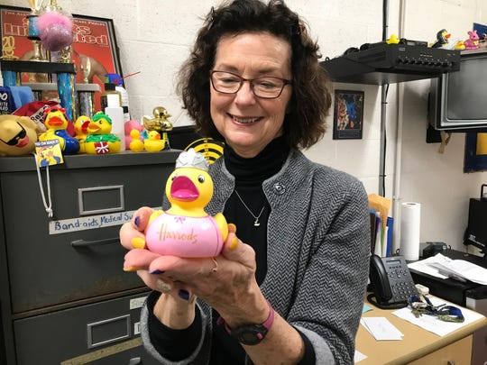 Ontario swim coach Debby Henry shows the rubber ducky one of her former swimmers brought back from Harrods, a famous department store in London