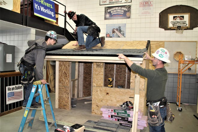 Tri-Rivers Career Center construction trades academy students Daniel Rengert, on ladder, and Will Ogden, on roof, work on a project with instructor Nardi Muka. Rengert is a junior from River Valley High School and Ogden is a junior from Upper Sandusky High School.