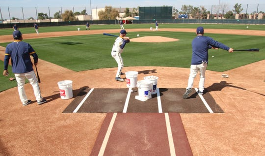 Brewers coaches spray grounders around the infield during fielding practice Tuesday.