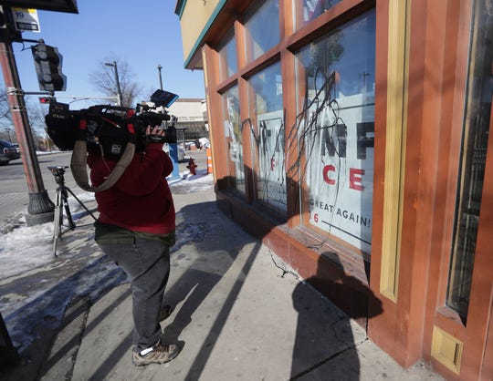A camera person records outside the vandalized Republican Party of Wisconsin field office at the northeast corner of North King Drive in Milwaukee.