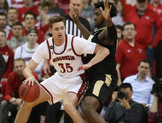 Feb 18, 2020; Madison, Wisconsin, USA; Wisconsin Badgers forward Nate Reuvers (35) works the ball against Purdue Boilermakers forward Trevion Williams (right) during the first half at the Kohl Center. Mandatory Credit: Mary Langenfeld-USA TODAY Sports
