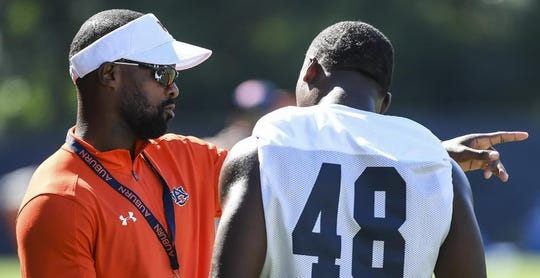 Auburn linebackers coach Travis Williams (left) coaches linebacker Montavious Atkinson during practice.