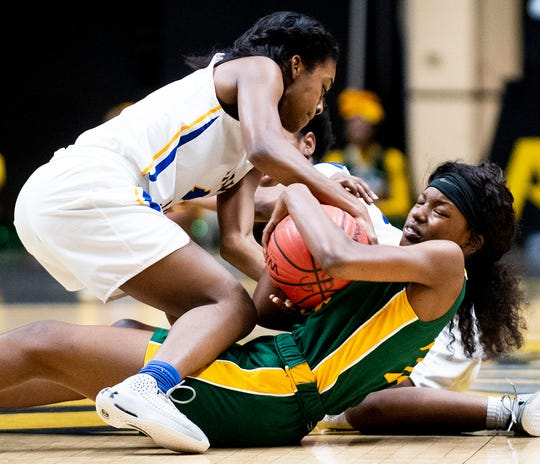 Aliceville's Zamarieuna Owens (1) and Central-Hayneville's Cordasia Harris (24) fight for possession in AHSAA regional action in Montgomery, Ala., on Wednesday February 19, 2020.