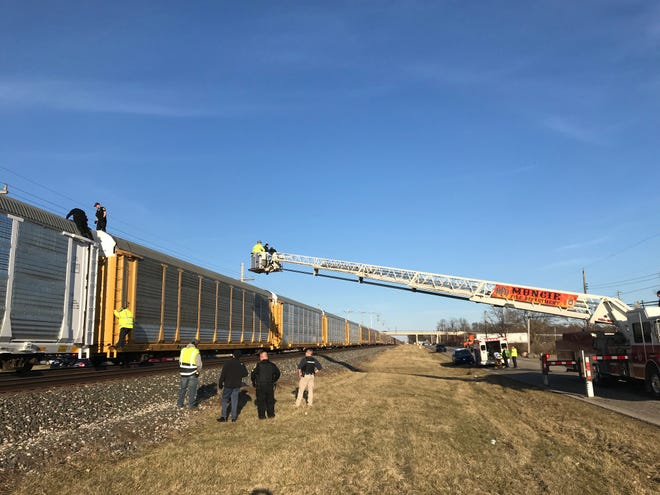 A ladder truck is used to get a subject off the top of a train stopped between Kilgore Avenue and Eighth Street.