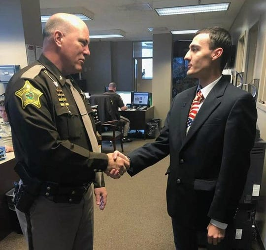 Matthew Peiffer shaking hands with Delaware County Sheriff Tony Skinner after he provided training on foster care children to his staff.