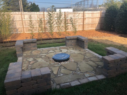 The fire pit has a seating area. The fence blocks the view of an electrical substation.