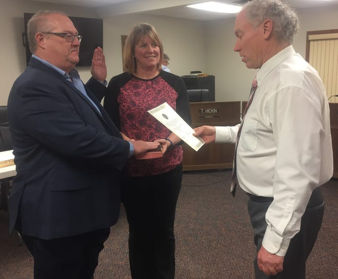 Left, councilman Tim Hickin (left) is sworn in by Mayor Mike Compton with wife, Tammy Hickin, looking on during the Jan. 6 Pataskala City Council meeting. Tim Hickin was also chosen as council vice president later in the meeting. He resigned his position in mid-February to seek the  position of city administrator.