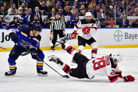 Feb 18, 2020; St. Louis, Missouri, USA;  St. Louis Blues left wing Jaden Schwartz (17) handles the puck as New Jersey Devils defenseman Damon Severson (28) falls to the ice during the first period at Enterprise Center.