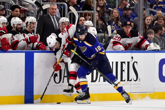Feb 18, 2020; St. Louis, Missouri, USA;  St. Louis Blues left wing Zach Sanford (12) checks New Jersey Devils right wing Nicholas Merkley (39) during the first period at Enterprise Center.