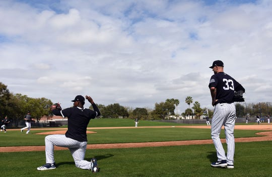 Feb 19, 2020; Tampa, Florida, USA; New York Yankees pitcher J.A. Happ (33) and pitcher Luis Severino (40) take part in a drill during spring training at George M. Steinbrenner Field.