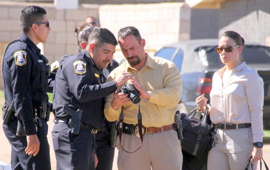 Deming Police Chief Alex Valdespino, left, and investigator James Fetrow scroll through crime scene photo images at the Silver Linings Thrift Store and Resource Center as officers and investigators look on.