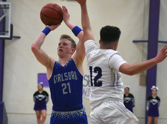 Carlsbad's Andrew Miller gets off a jumper as Clovis' Blake Muscato defends in the third quarter of Tuesday's District 4-5A game at Rock Staubus Gymnasium.