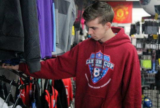 Josh Posuniak, an employee at the Soccer Plus store in Livonia and a Canton resident, adjusts jerseys at the store at Five Mile and Newburgh.
