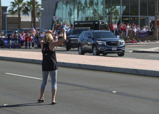 Sue Stewart of Palm Springs boos and gives a thumbs down to President Trump's motorcade on Hwy 111 after his visit Porcupine Creek in Rancho Mirage, February 19, 2020.
