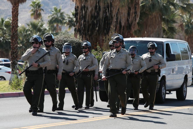 Law enforcement with riot gear approach Highway 111 near Indian Trail in Rancho Mirage, Calif., on Wednesday, February 19, 2020.