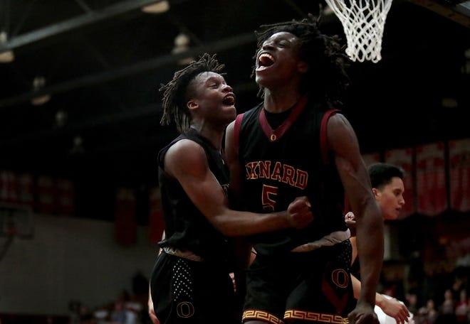 Stacy Johnson, left, and Kai Johnson celebrate during Oxnard's overtime win at Palm Springs High on Tuesday night. The Yellowjackets will play at Hesperia on Friday night in a CIF-SS Division 2A semifinal game.