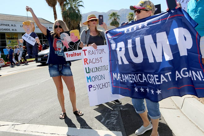 President Trump supporter Vicki Haeberle, right, of La Quinta holds a Trump banner as protesters demonstrate against the President on Highway 111 near Indian Trail in Rancho Mirage, Calif., on Wednesday, February 19, 2020.