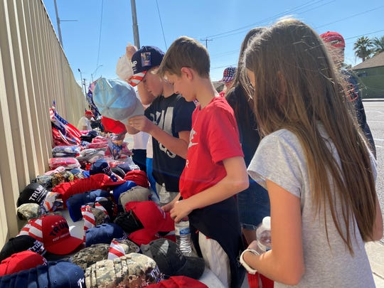 Children attending a President Donald Trump rally look at Blake Warren's hats lined up on tables outside Veterans Memorial Coliseum on Feb. 19. 2020.