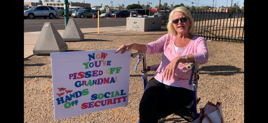 Bonnie Oakes holds a sign protesting President Donald Trump on Feb. 19, 2020.