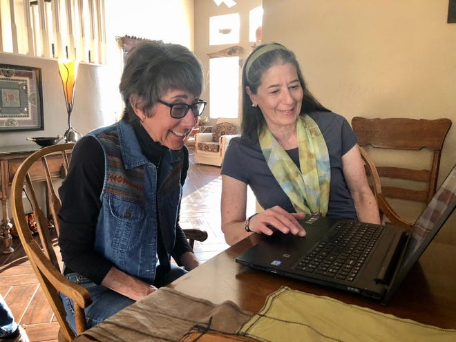 Shari Keith and her half-sister Judy Greenfield look at family pictures together.