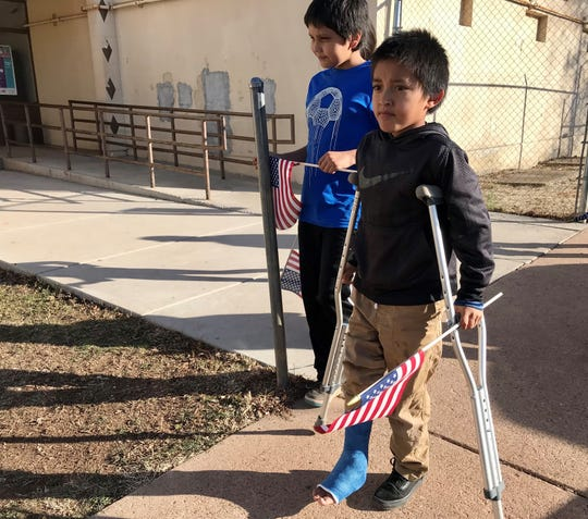 Eight-year-old Isaac Opah walks with his crutches alongside Ulven Luppe, 11, to place a flag at the memorial set up in front of the White Mountain Apache Police Department on Feb. 18, 2020.
