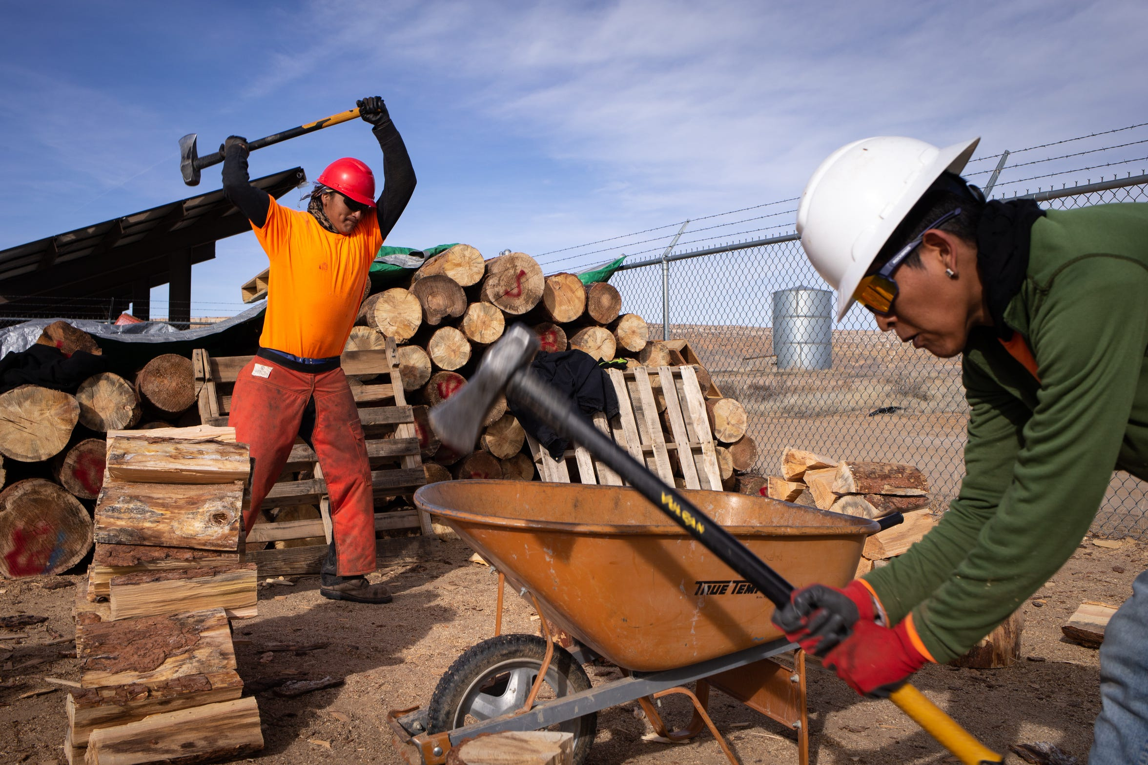 Ahgoon Honie (left) and Andre Lucas, both Wood Project crew members, split wood on Feb. 6, 2020, at the Tewa administration building on the Hopi Reservation.