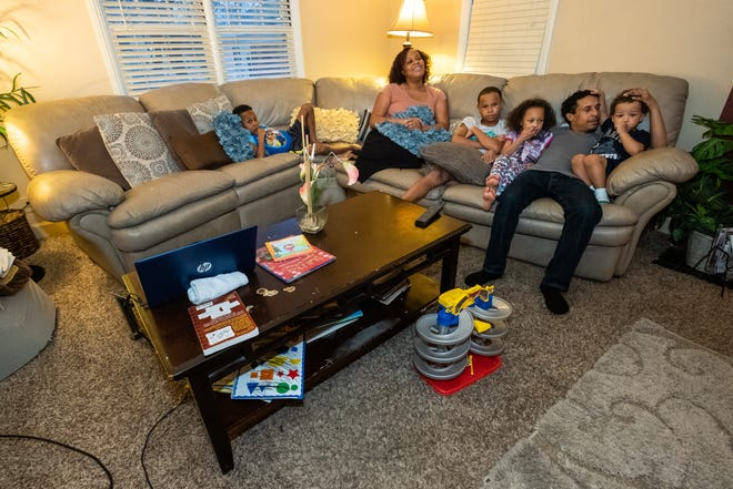 Dalayna McDade-Stepp, second from left, sits with her family Monday, Feb. 17, 2020, in the living room of their Port Huron home. McDade came to Port Huron with her six children several years ago and credits SONS as a big help for them to get their footing in the city.